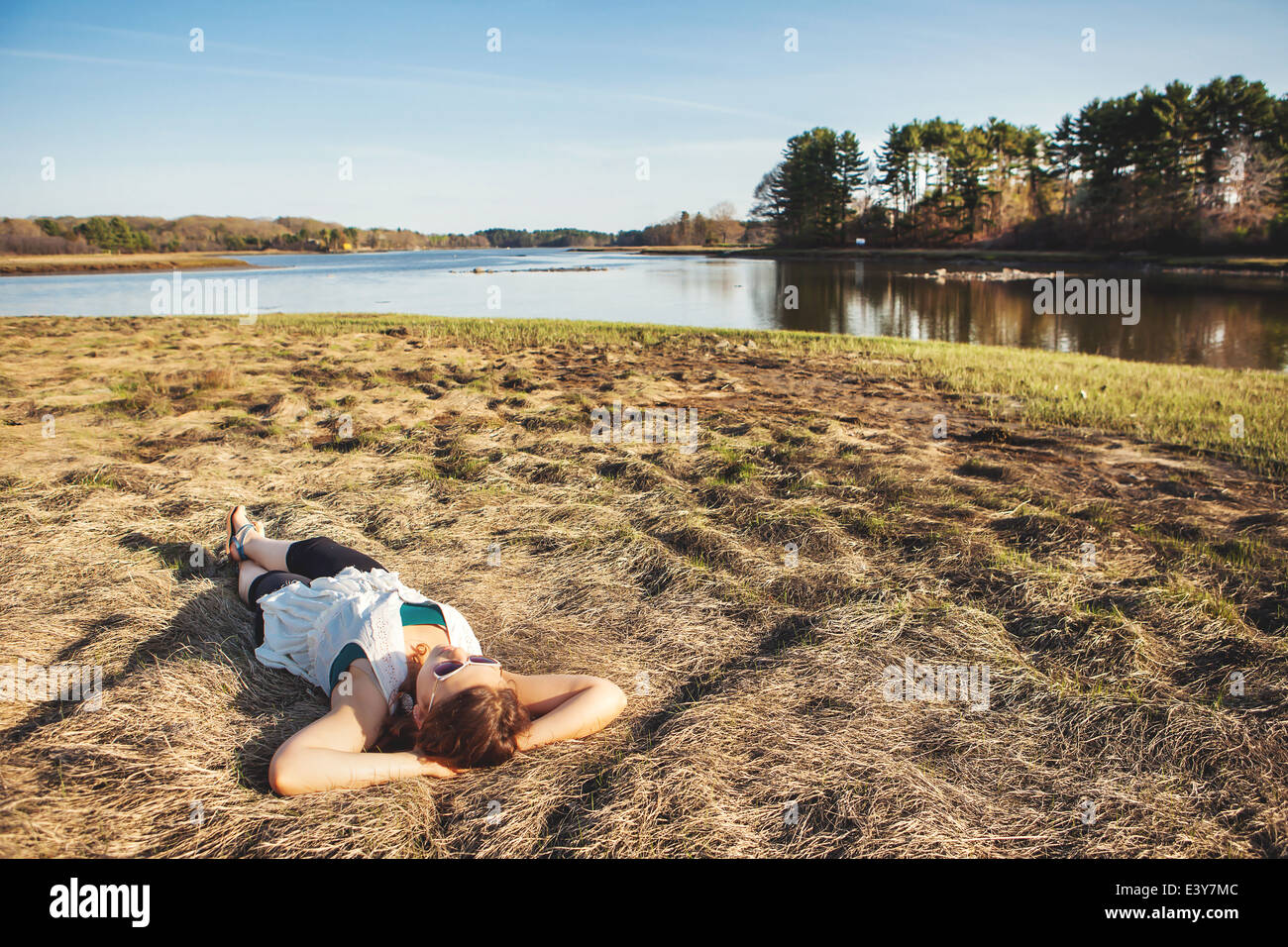 Young woman sunbathing on grass in Kittery, Maine, USA - Stock Image