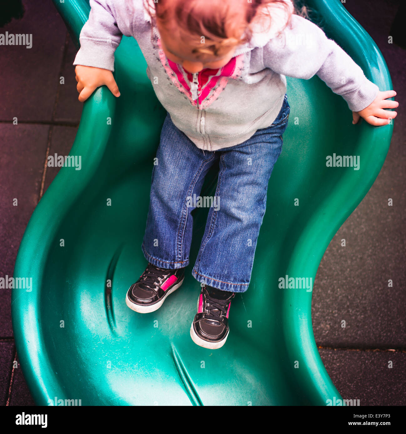 Toddler going down slide in playground - Stock Image
