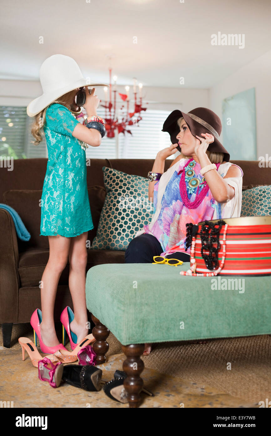 Mother and daughter dressing up in hats and high heels - Stock Image