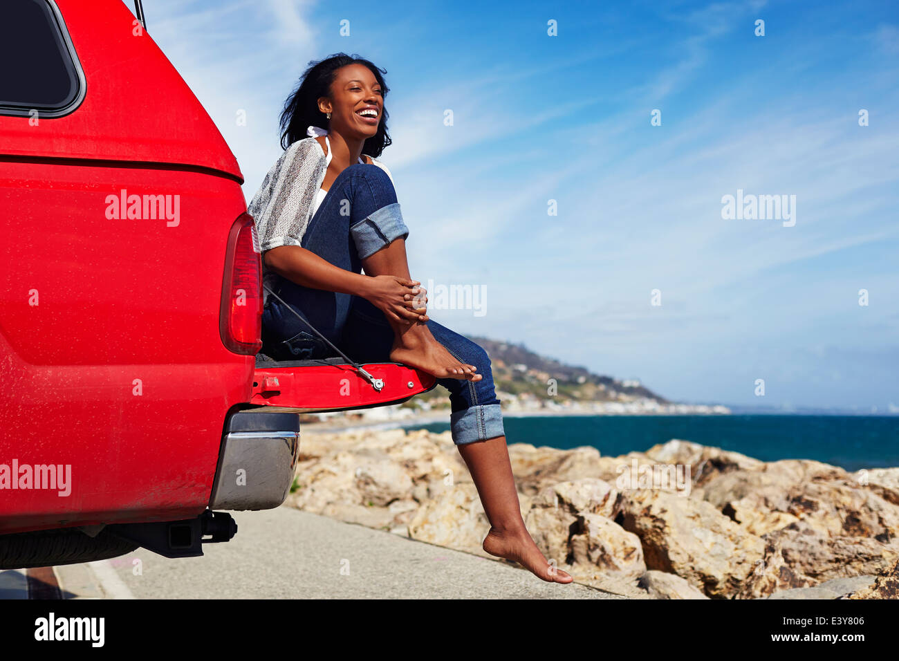 Young woman sitting on car hood, Malibu, California, USA - Stock Image