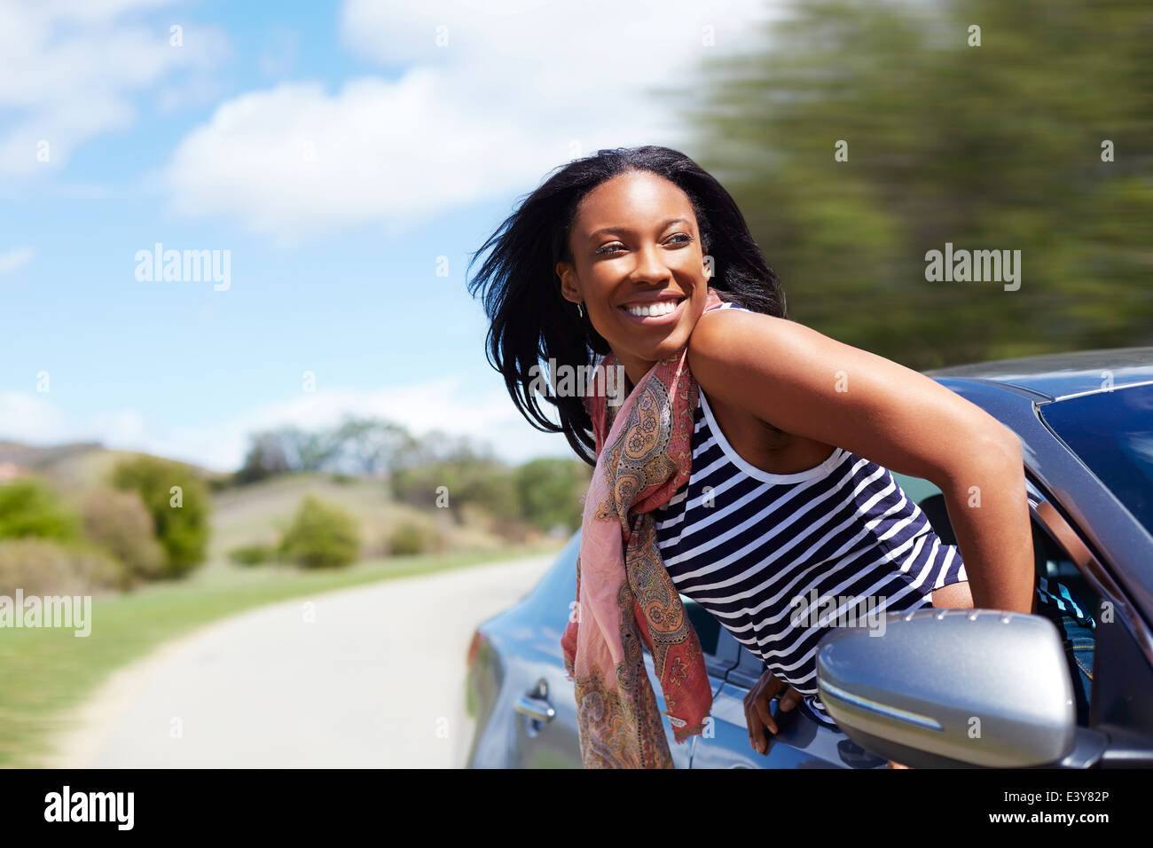 Young woman leaning out of moving car window - Stock Image