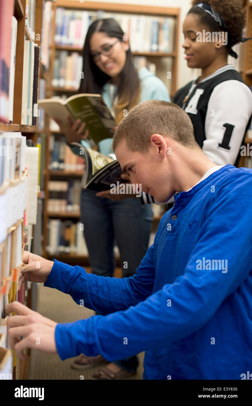College students choosing books in library - Stock Image