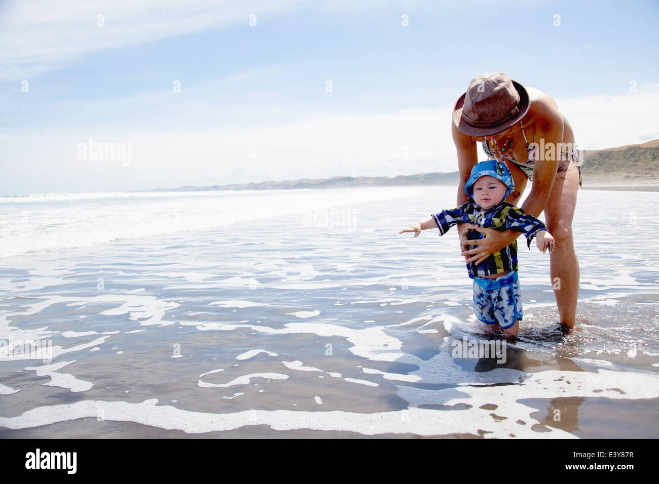 Young woman paddling in sea with baby son - Stock Image