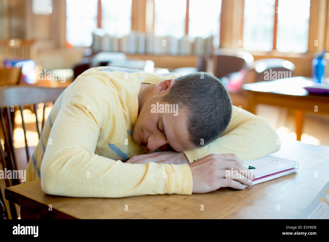Young man asleep on book - Stock Image
