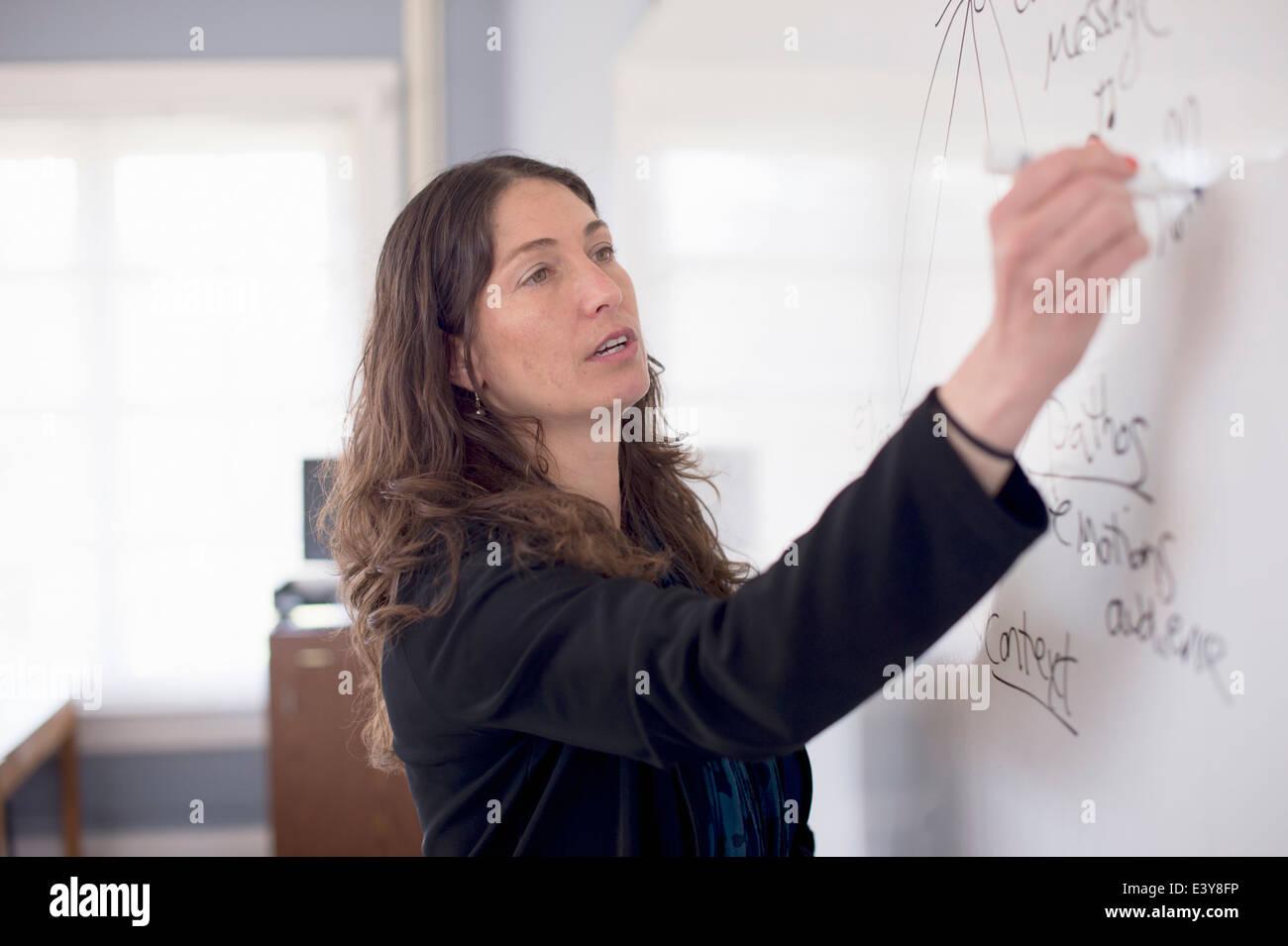 Teacher writing on whiteboard - Stock Image