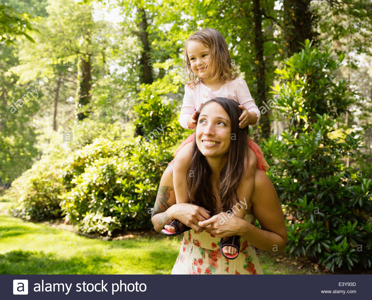 Mother giving toddler daughter a shoulder carry in park - Stock Image