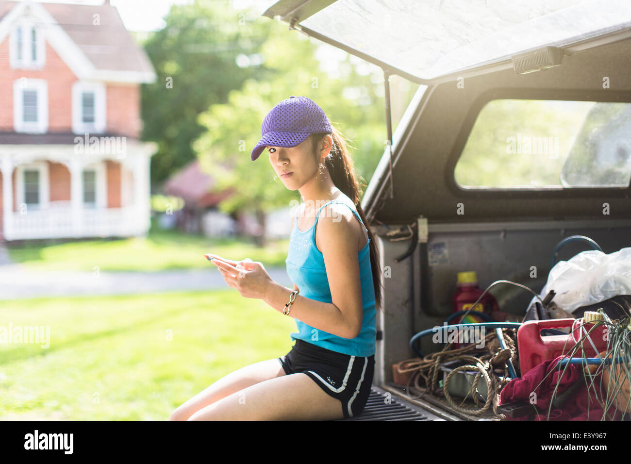Portrait of teenage girl, sitting on open car boot Stock Photo