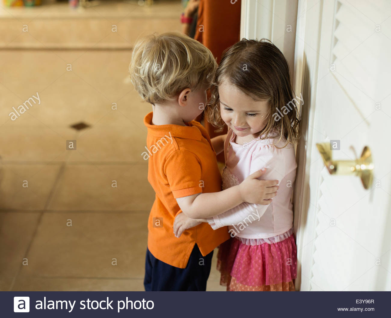 Male and female toddler friends with arms around each other - Stock Image