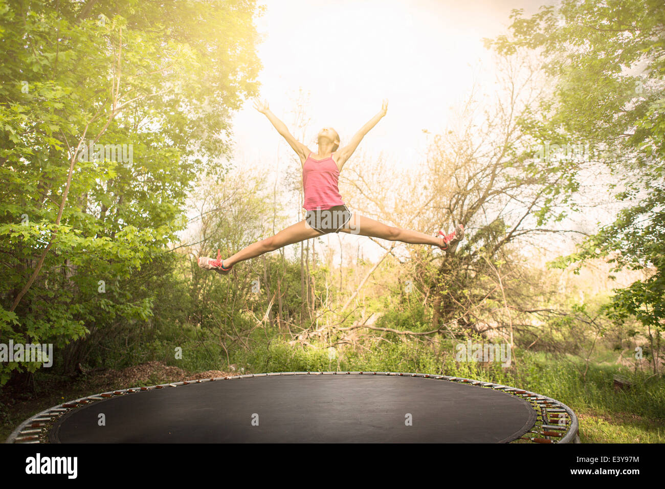 Teenage girl doing star jump on trampoline, outdoors - Stock Image