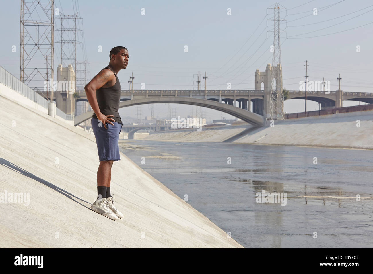 Young male runner taking a break on city riverbank - Stock Image