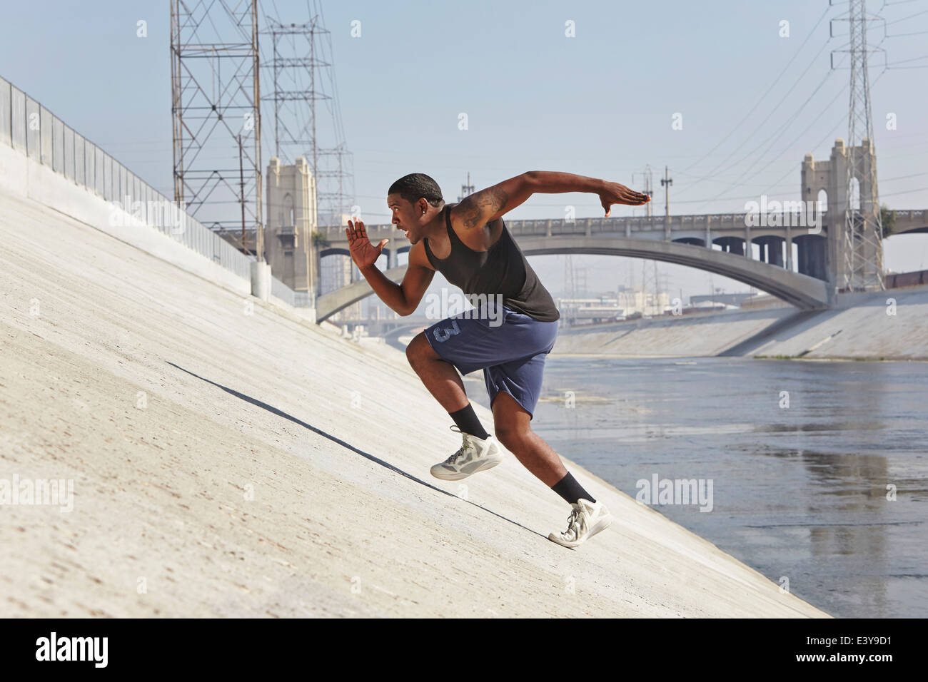 Young man speed running up riverbank - Stock Image