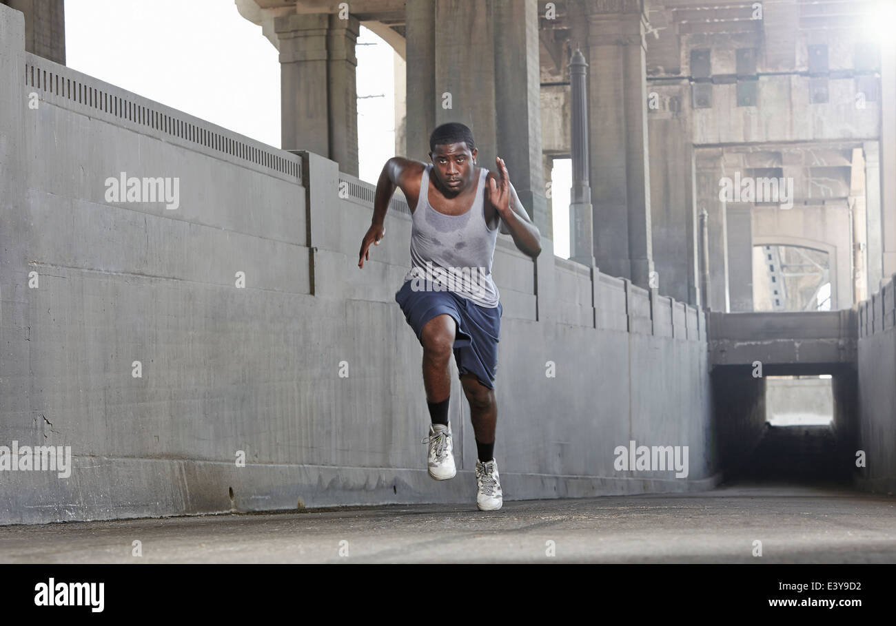 Young man speed running over city bridge - Stock Image