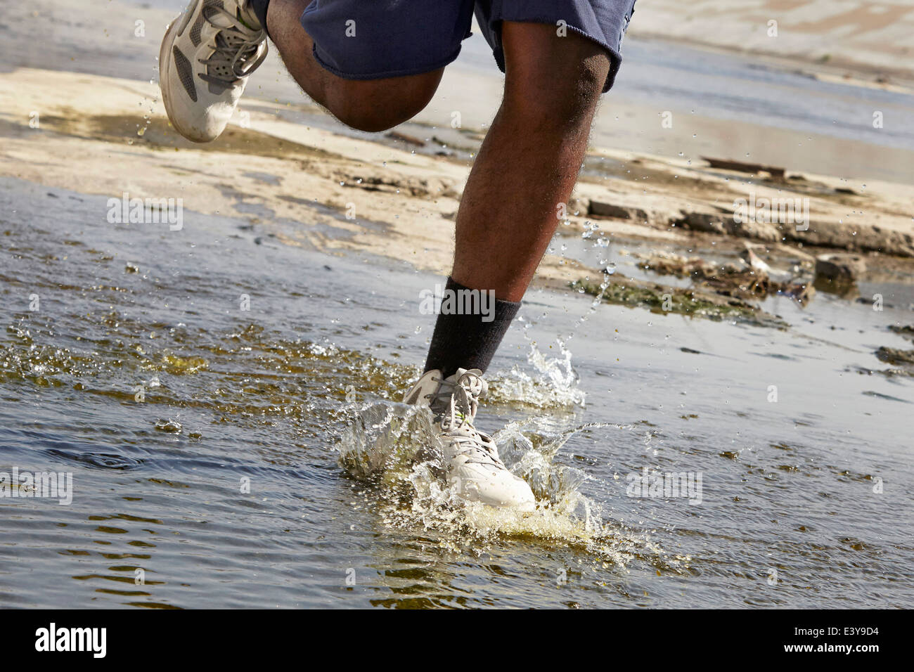 Cropped view of young man running through river - Stock Image