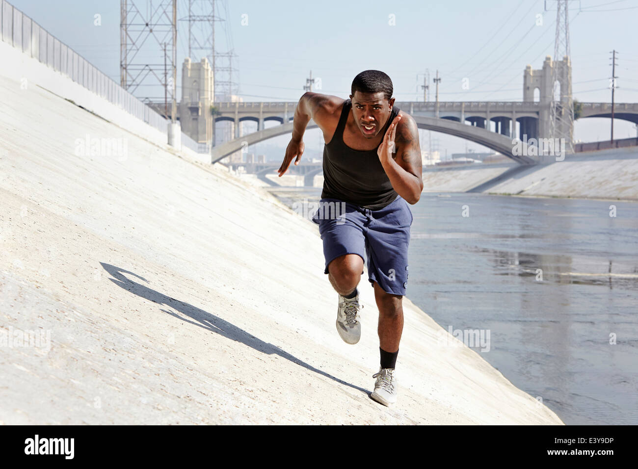 Young man speed running along riverbank - Stock Image