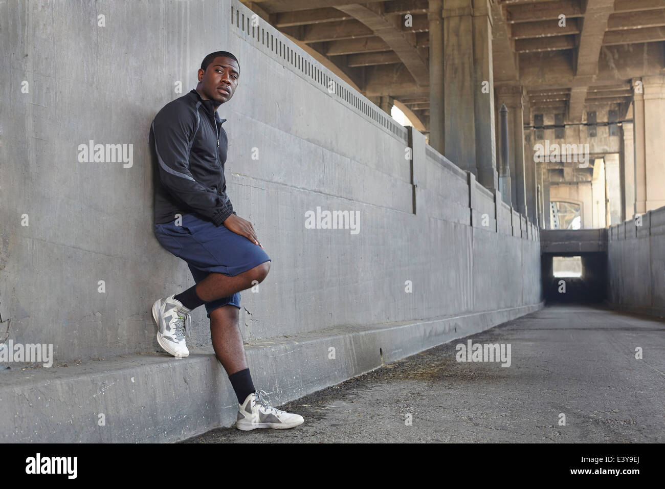 Young male runner taking a break on city bridge - Stock Image
