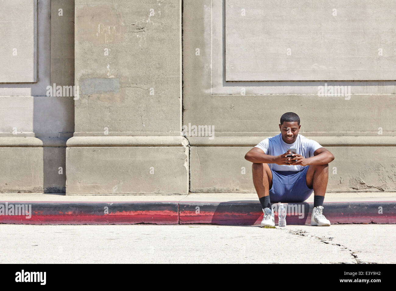 Young male runner sitting on sidewalk texting on smartphone - Stock Image