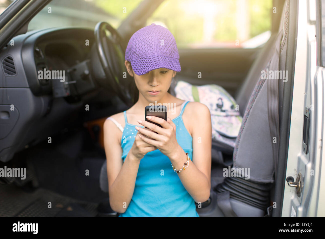 Teenage girl standing beside open car, using mobile phone - Stock Image