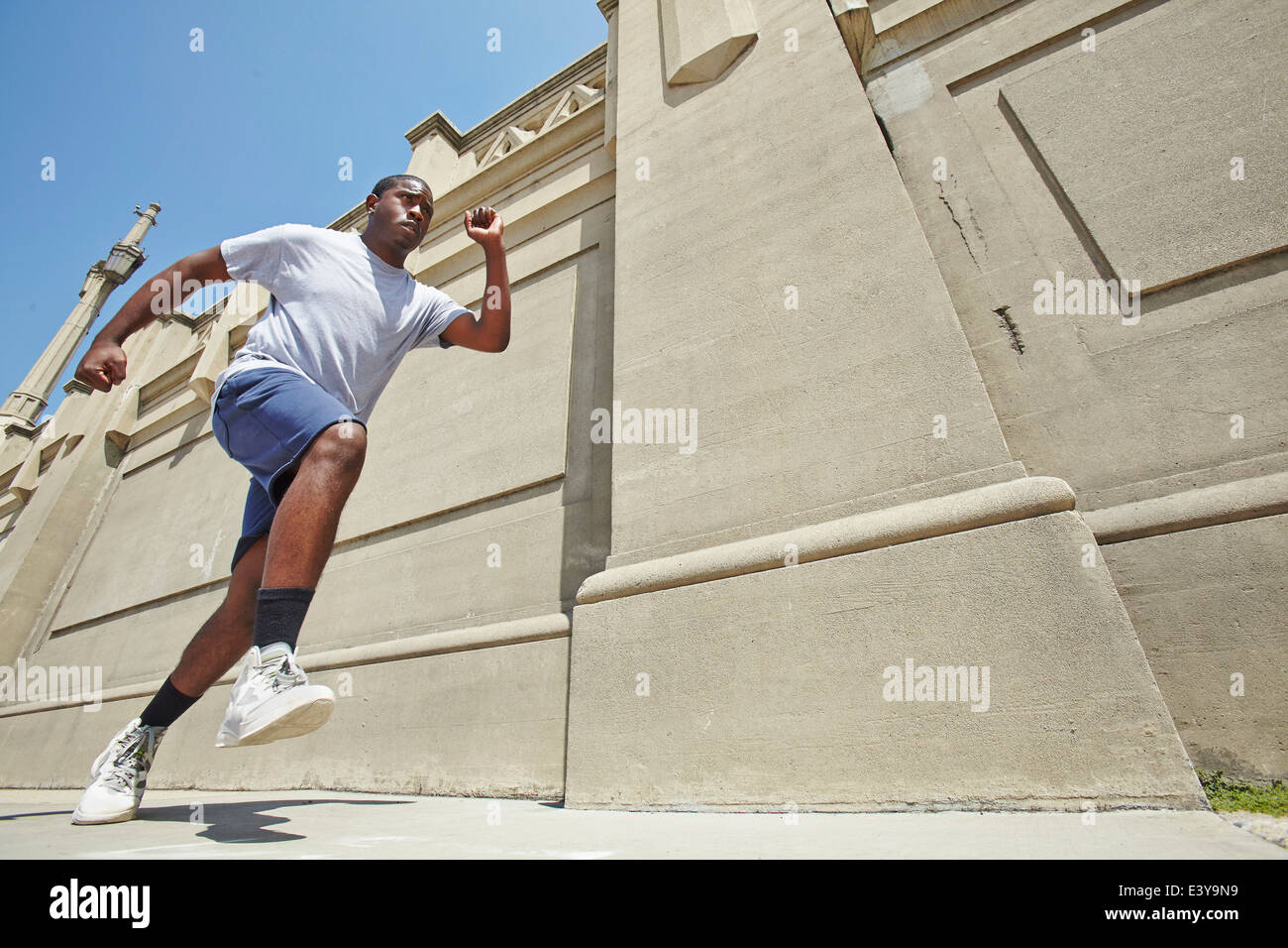 Low angle view of young man speed running - Stock Image
