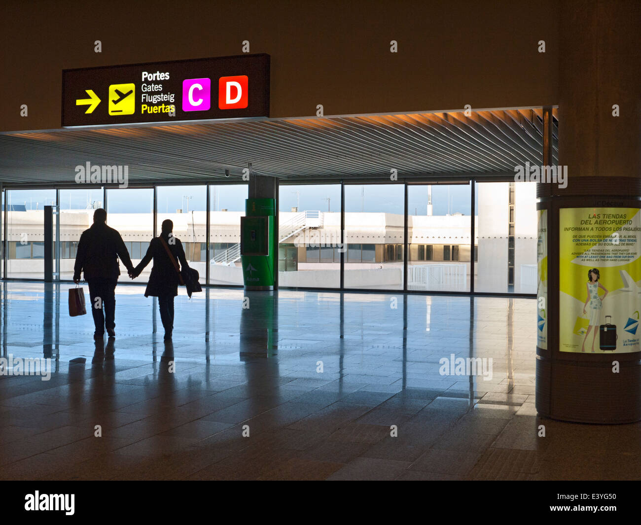 AIRPORT SPAIN Couple with duty free shopping bags walking hand in hand to airline departures gate in modern Spanish Stock Photo