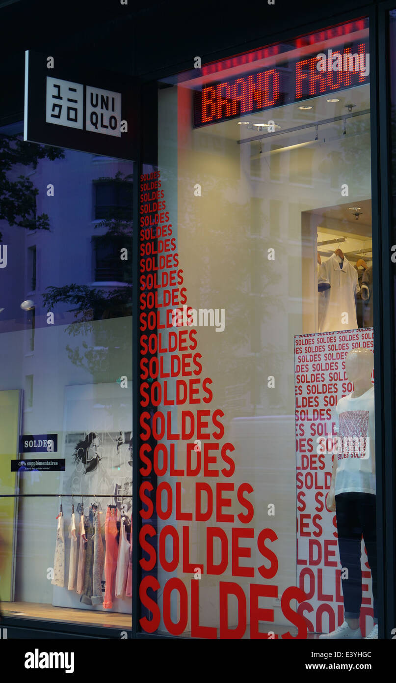 Summer sales in Paris reflected in Uniqlo show window - Stock Image