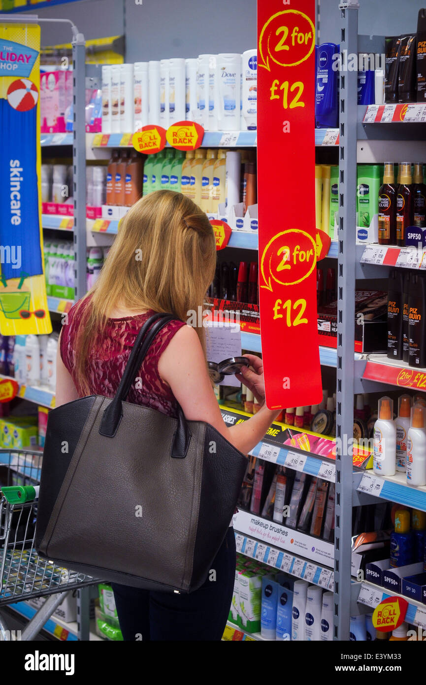 young woman shopping for skincare at supermarket - Stock Image
