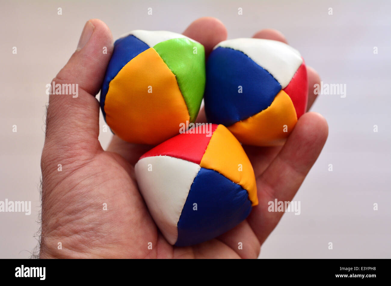 Man holds three (3) Juggling balls on one hand (left) against light background. concept photo, copy space - Stock Image