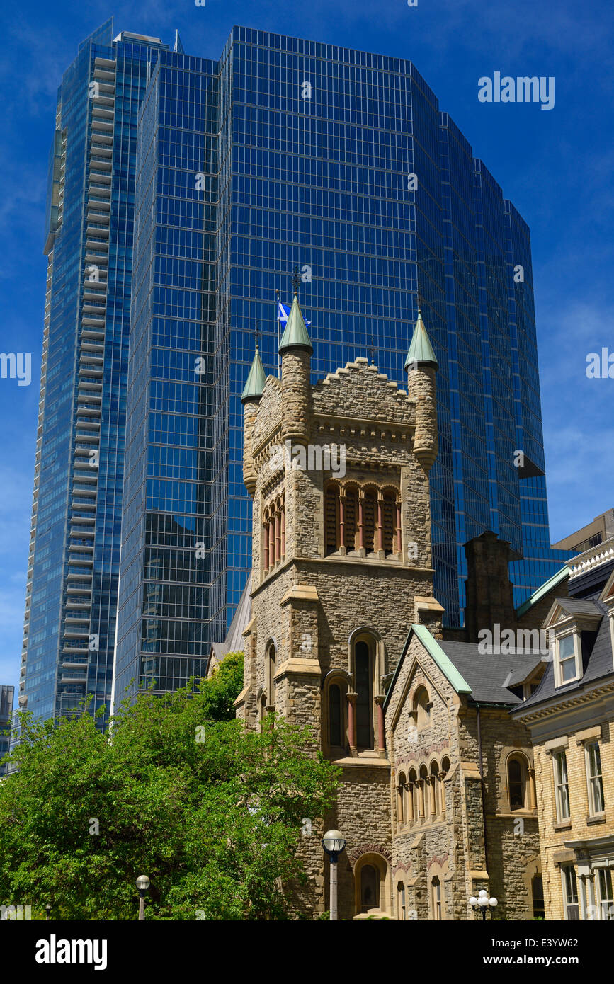 Old St Andrews presbyterian church tower against modern blue glass highrise office tower Toronto - Stock Image
