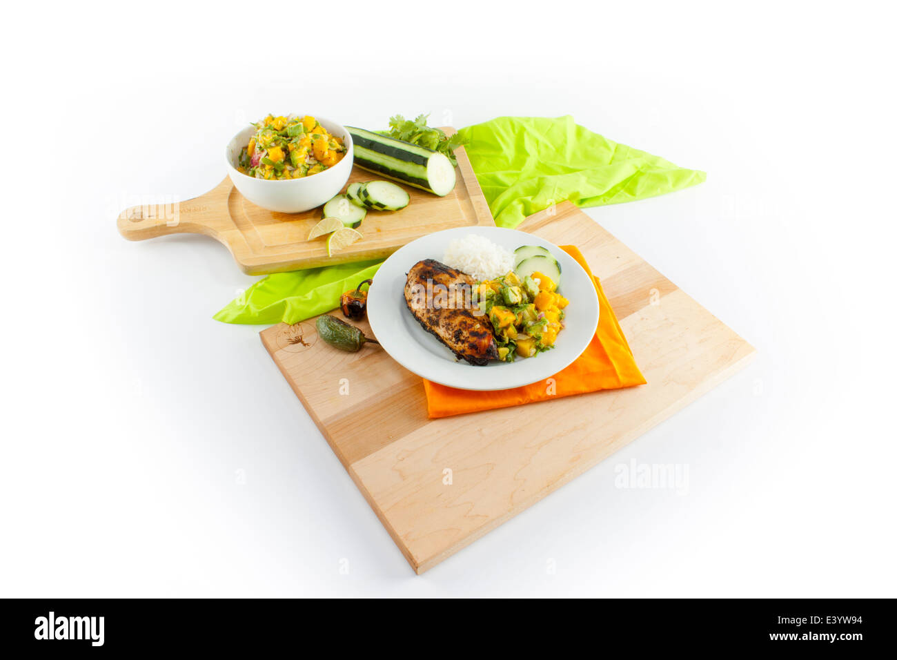 Layout of chicken meal on cutting boards. Sliced cucumber, mangos, and salad bowl. Optional cut out. - Stock Image