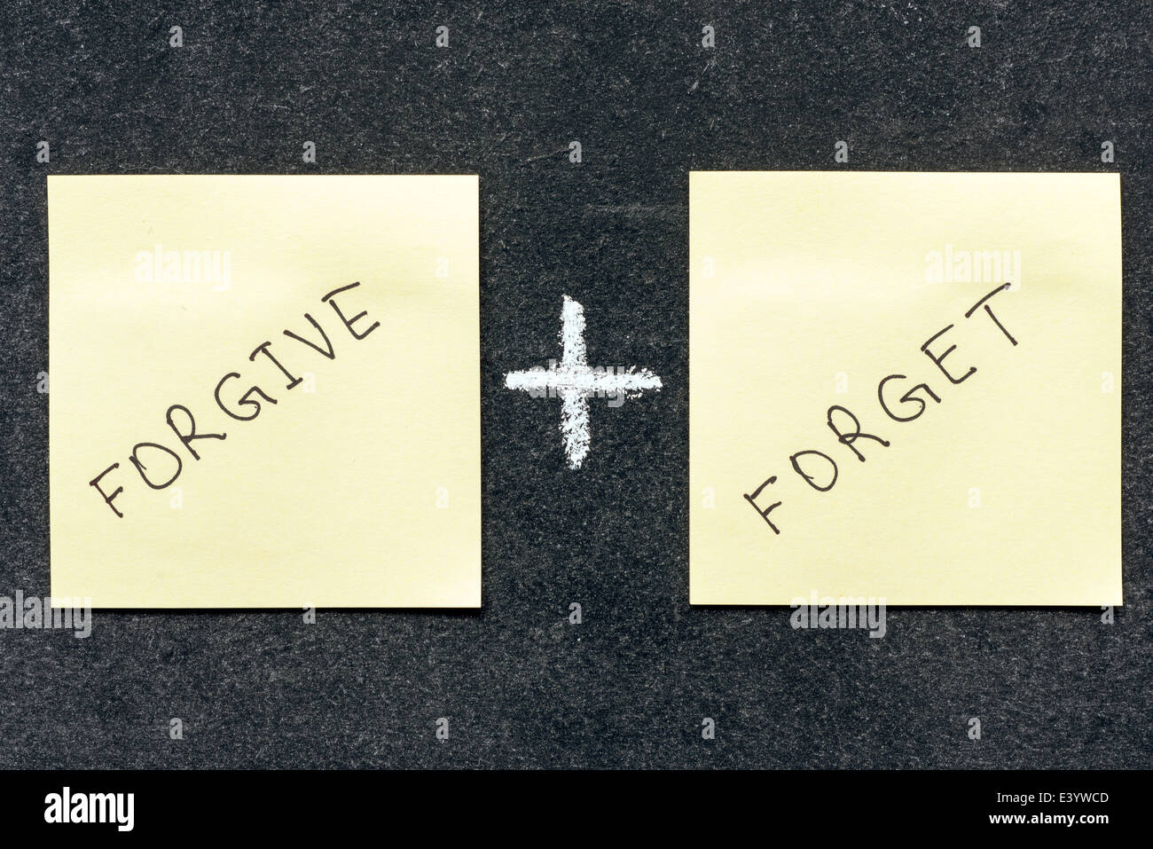 forgive and forget words handwritten on sticker notes - Stock Image