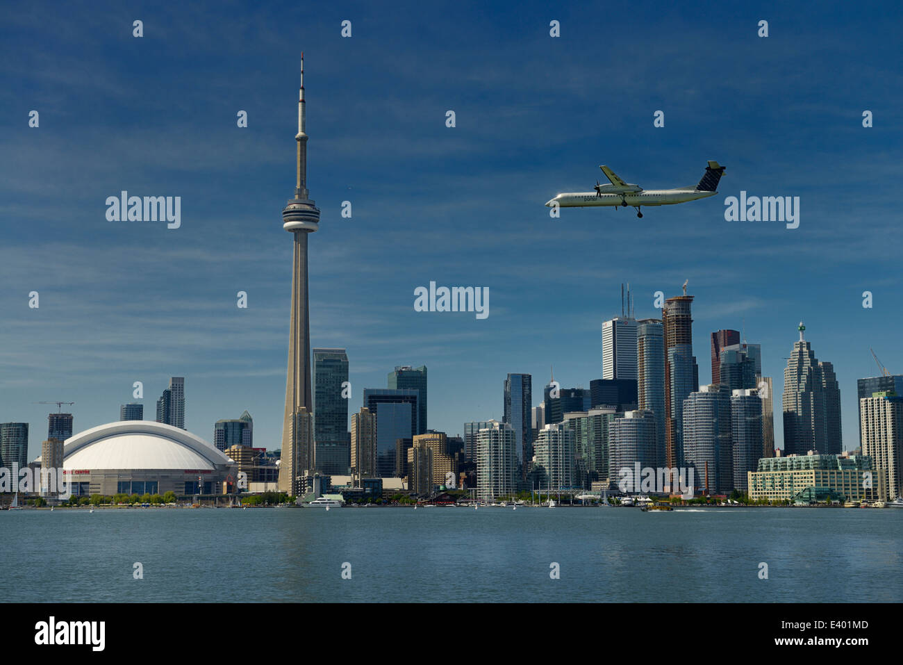Toronto skyline with Rogers Centre CN Tower condo and financial towers and Porter airplane landing on Island Airport - Stock Image