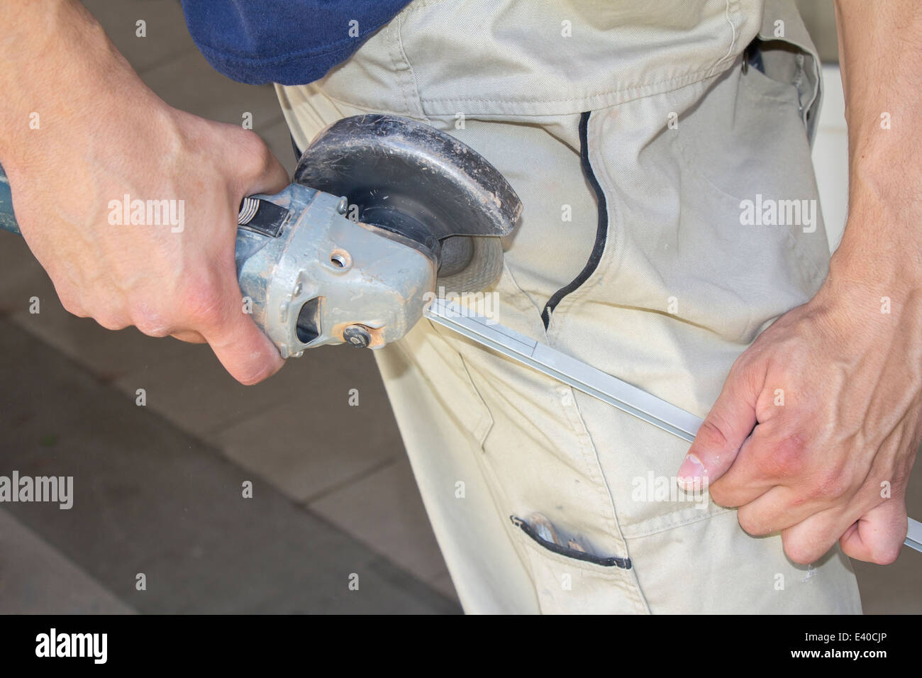 Worker cutting aluminum with angle grinder in workshop - Stock Image