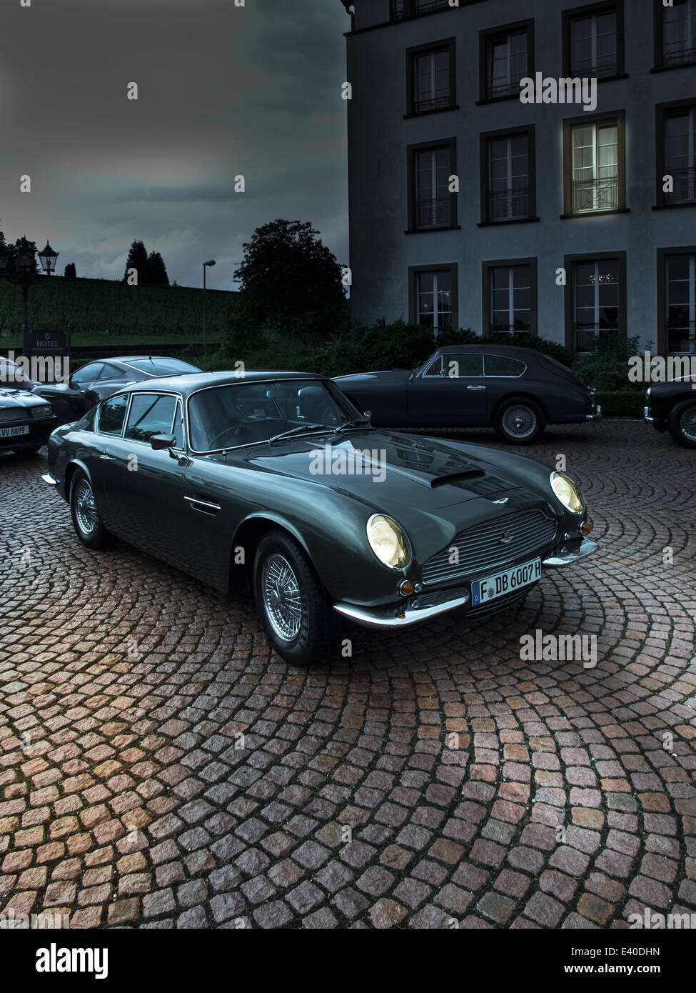Parking Aston Martin DB 6 with lighted headlights - Stock Image
