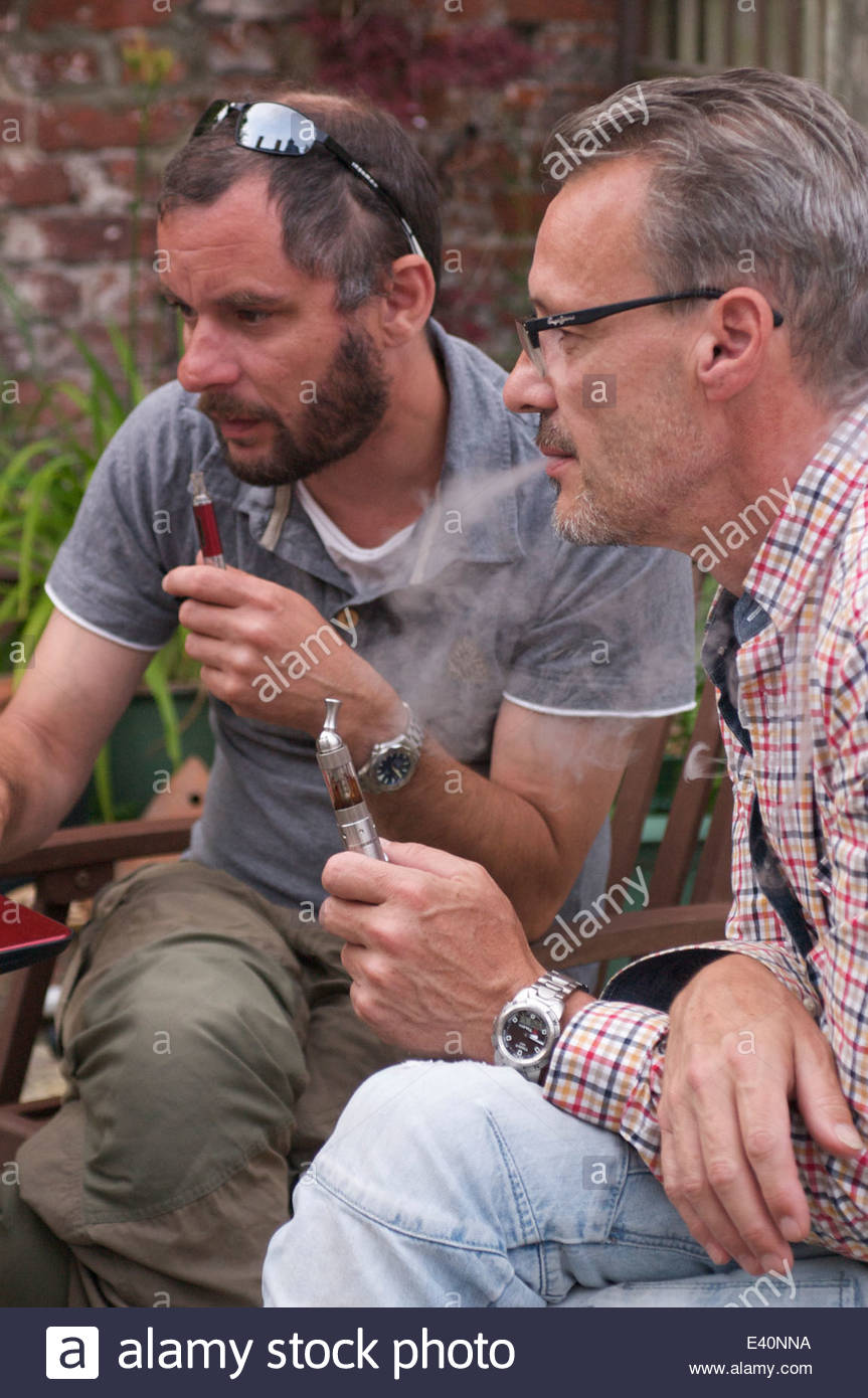 Two men in a garden puffing on electronic pipes, known as 'Vaping' whilst concentrating  on a laptop which - Stock Image