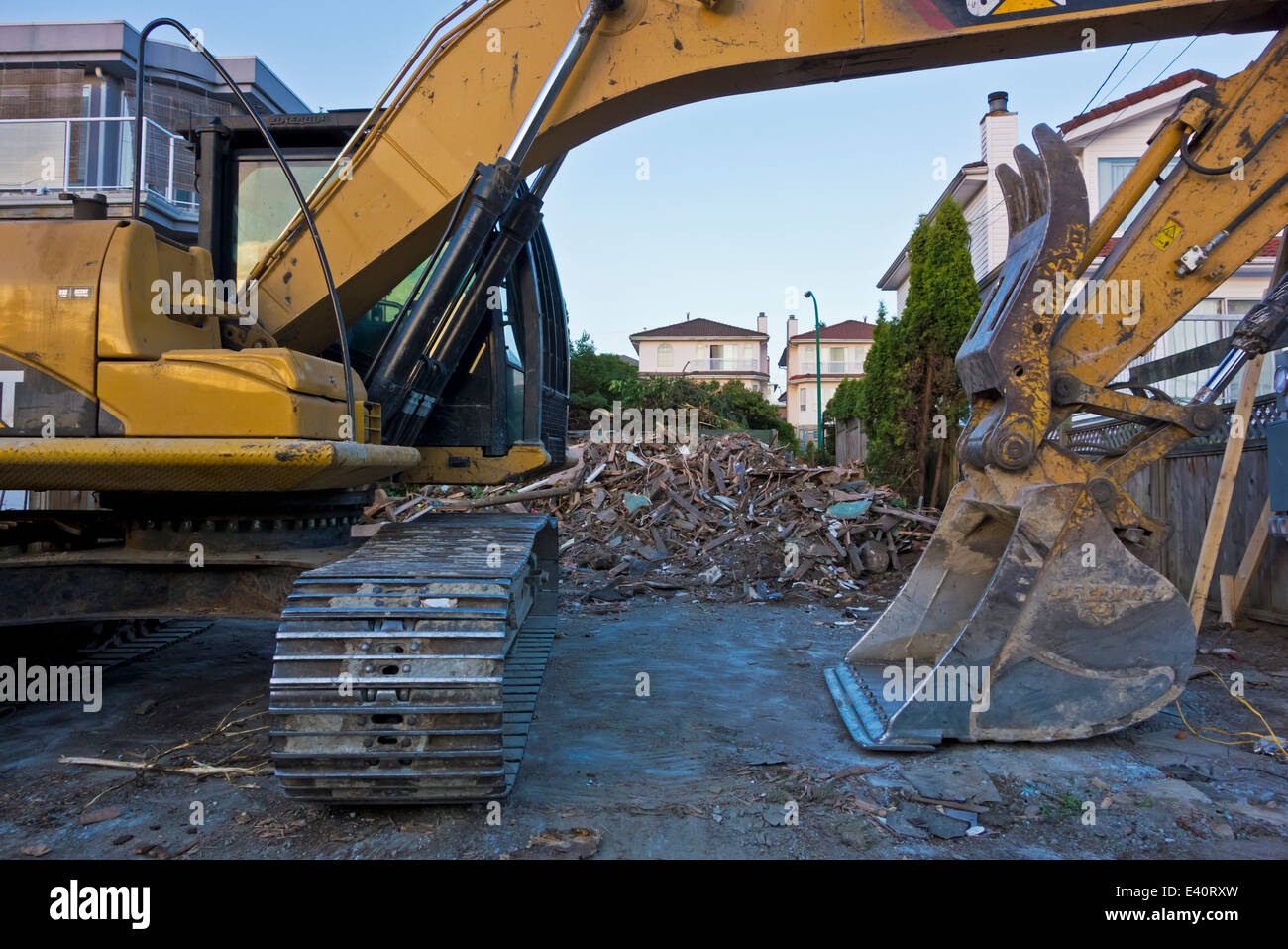 Backhoe with the rubble of a torn down house in Burnaby, suburb of Vancouver.  Tear down to build a newer home. - Stock Image