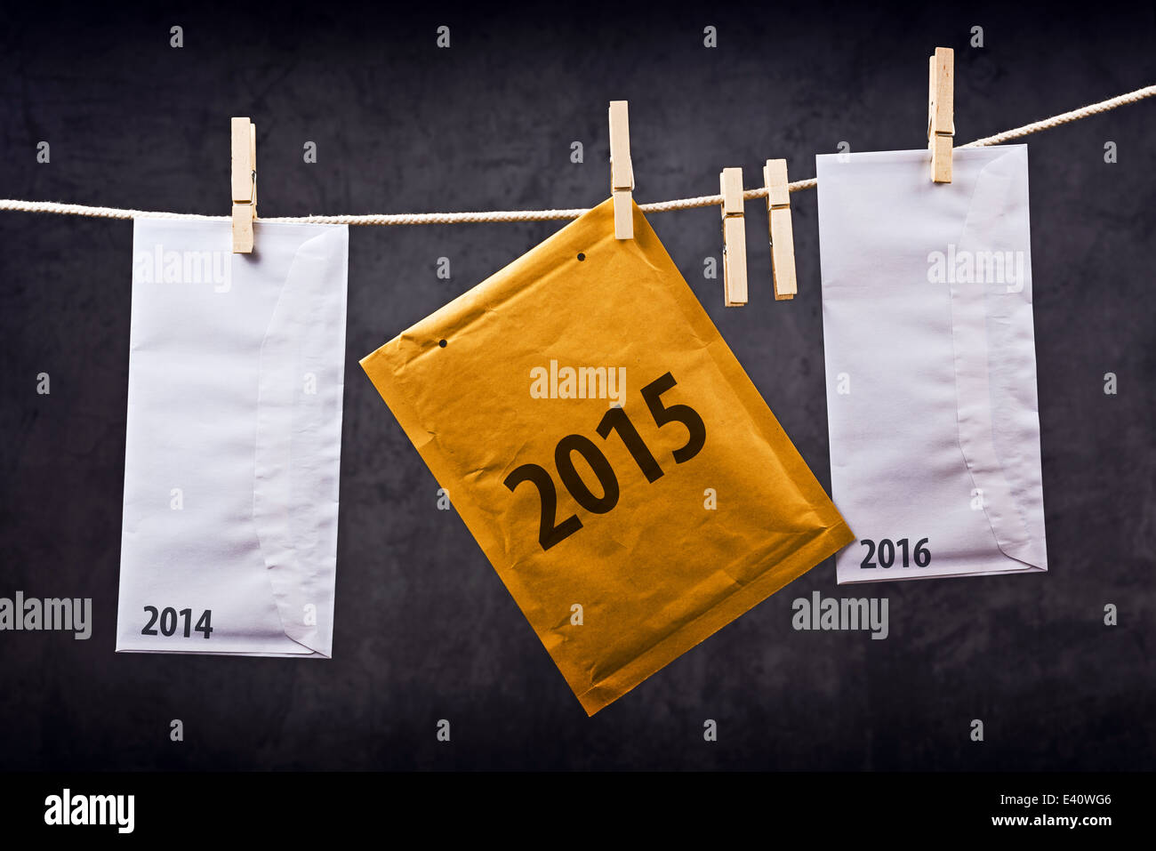 Three Postal mail Envelopes with year numbers 2014, 2015 and 2016 hanging on rope attached with clothes pins. - Stock Image