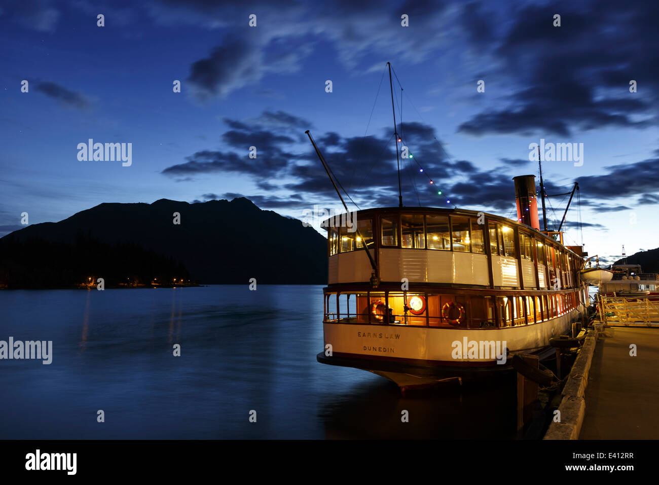New Zealand, Queenstown, lighted passenger ship lying at quai - Stock Image