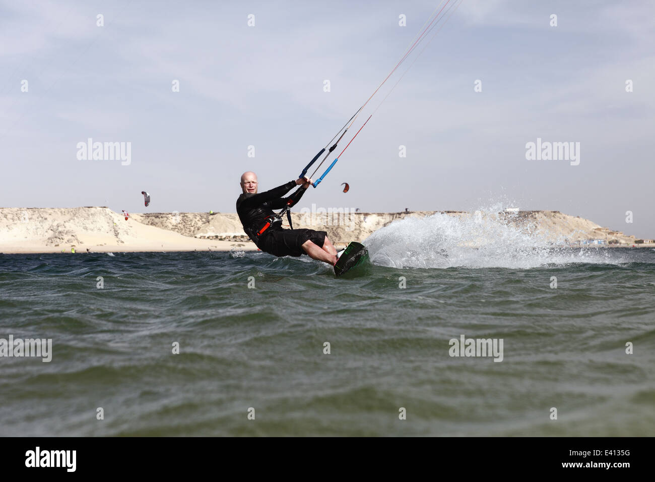 Man kitesurfing towards the photographer on the lagoon in Dakhla, Western Sahara, Morocco - Stock Image