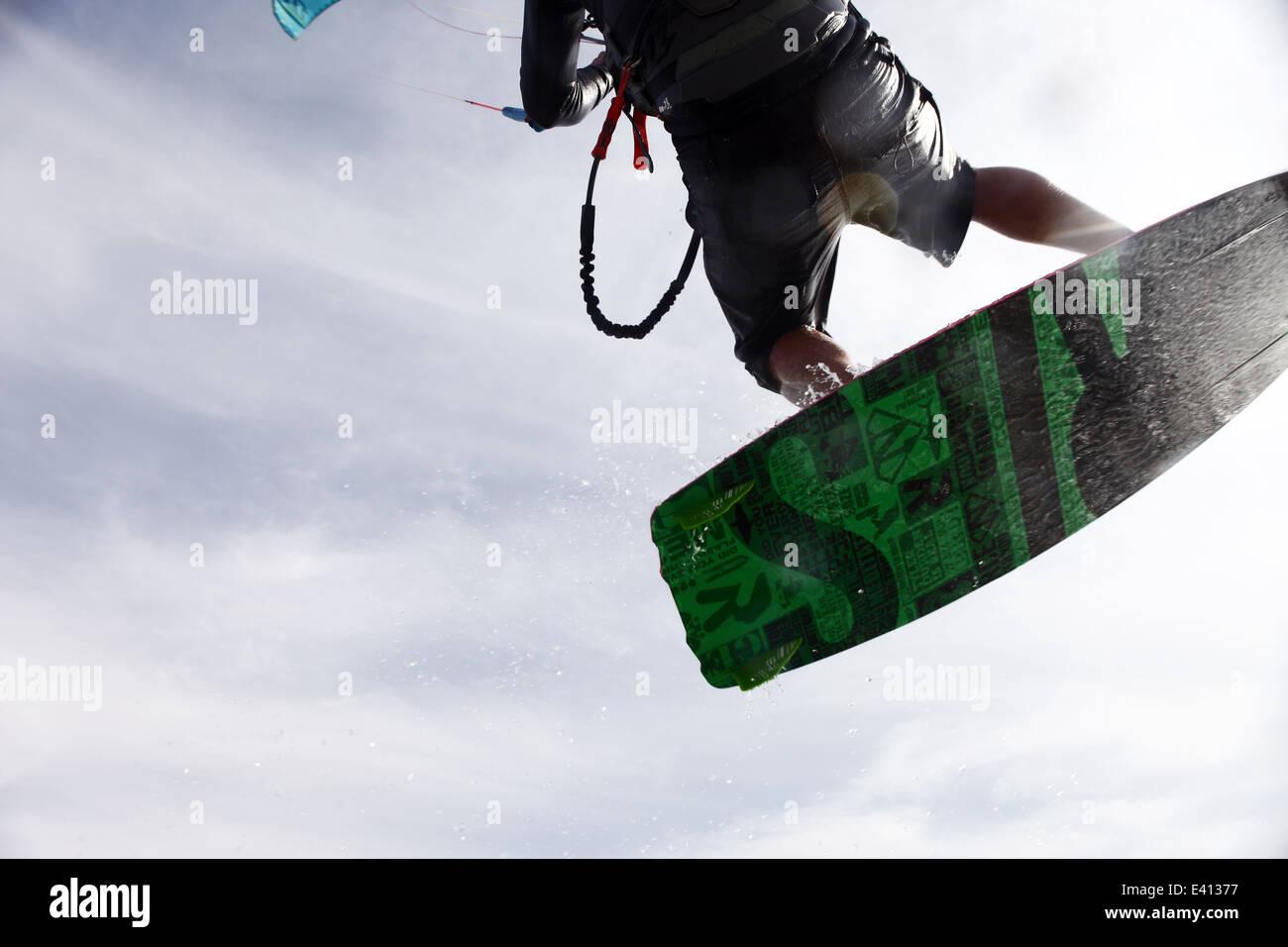 Man kitesurfing doing a jump on the lagoon in Dakhla, Western Sahara, Morocco - Stock Image