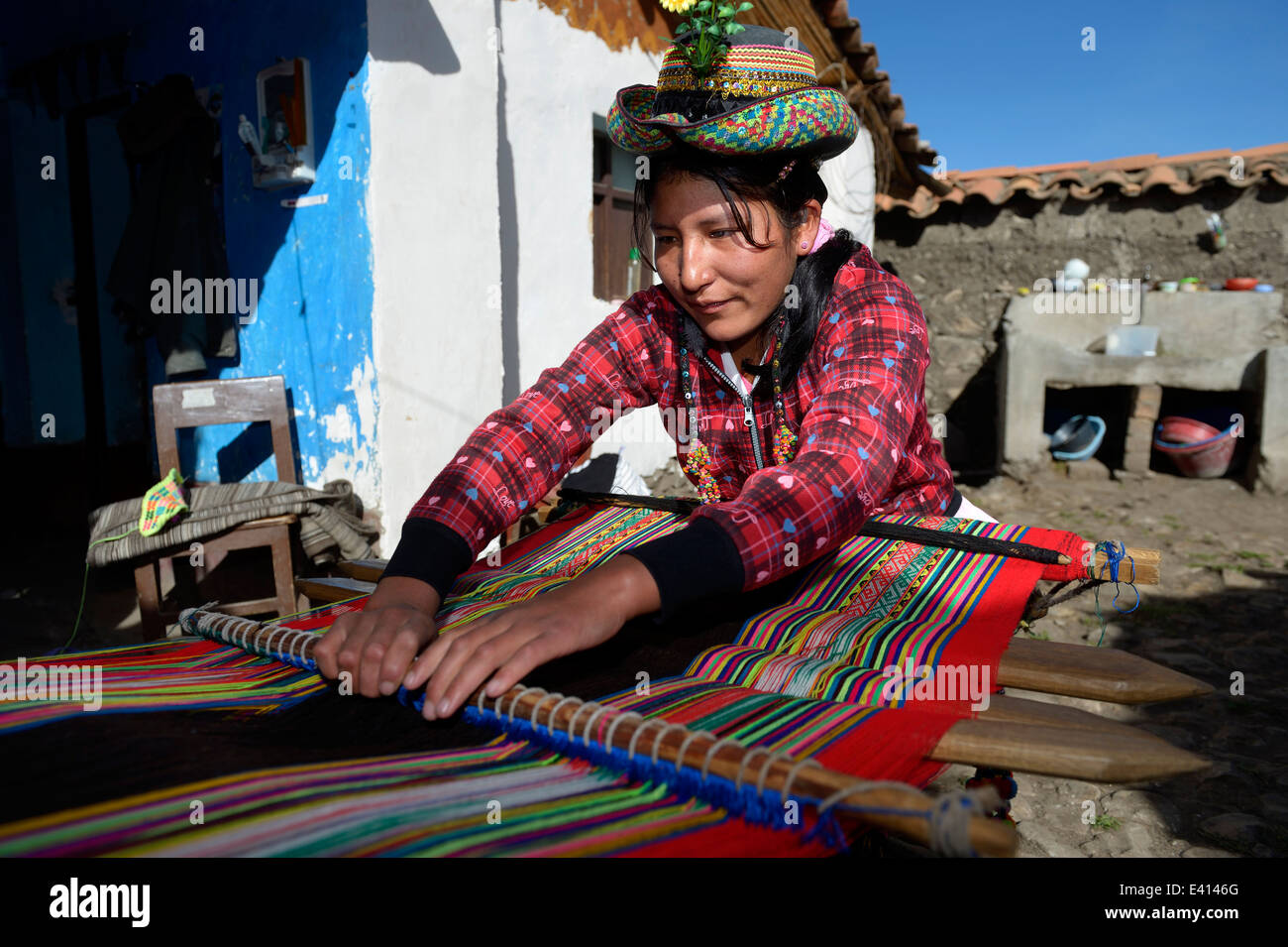 Peru, Quispillacts, Young woman weaving traditional cloth - Stock Image