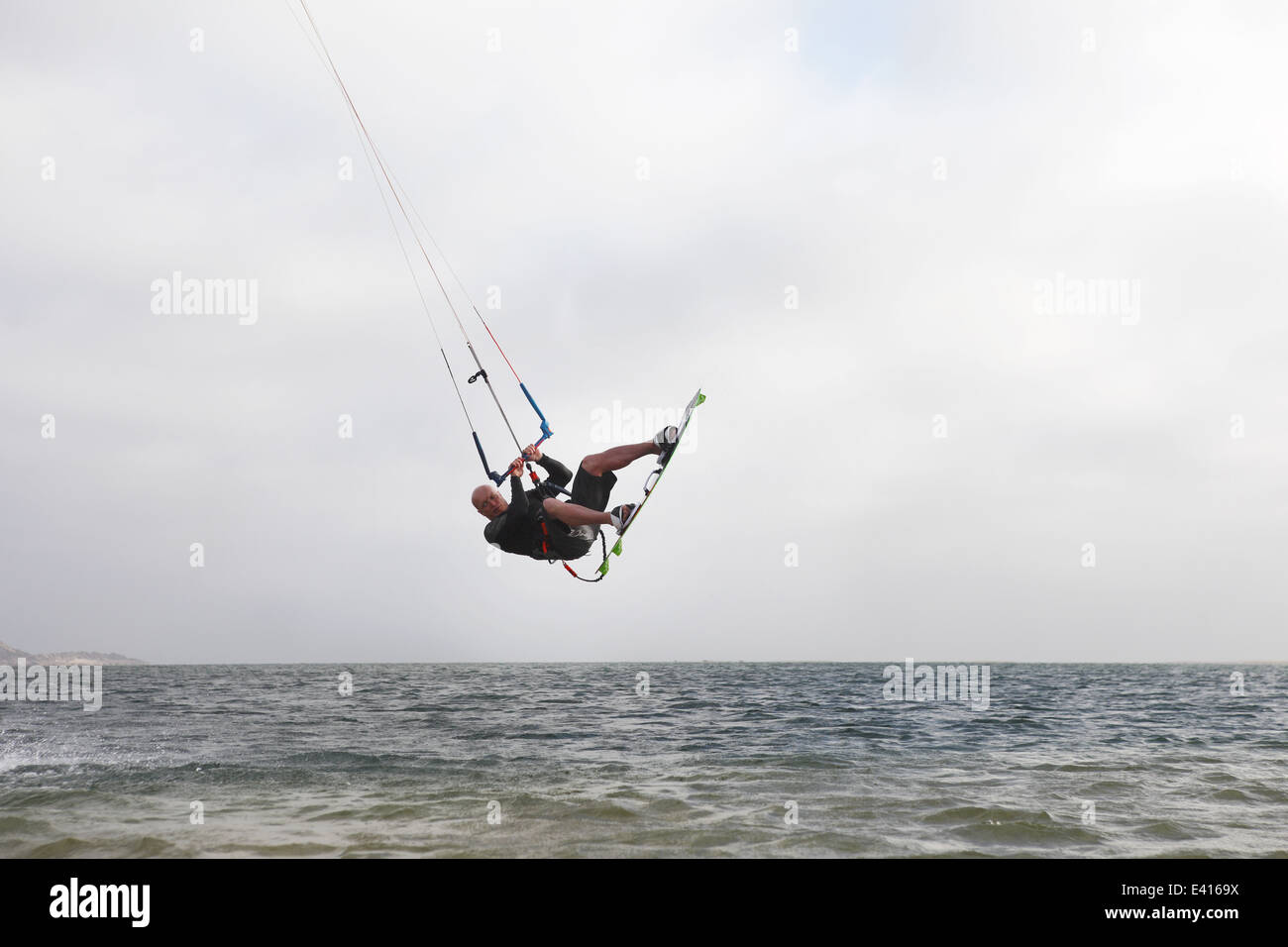 Man kitesurfing a jump on the horizon of the lagoon in Dakhla, Western Sahara, Morocco - Stock Image