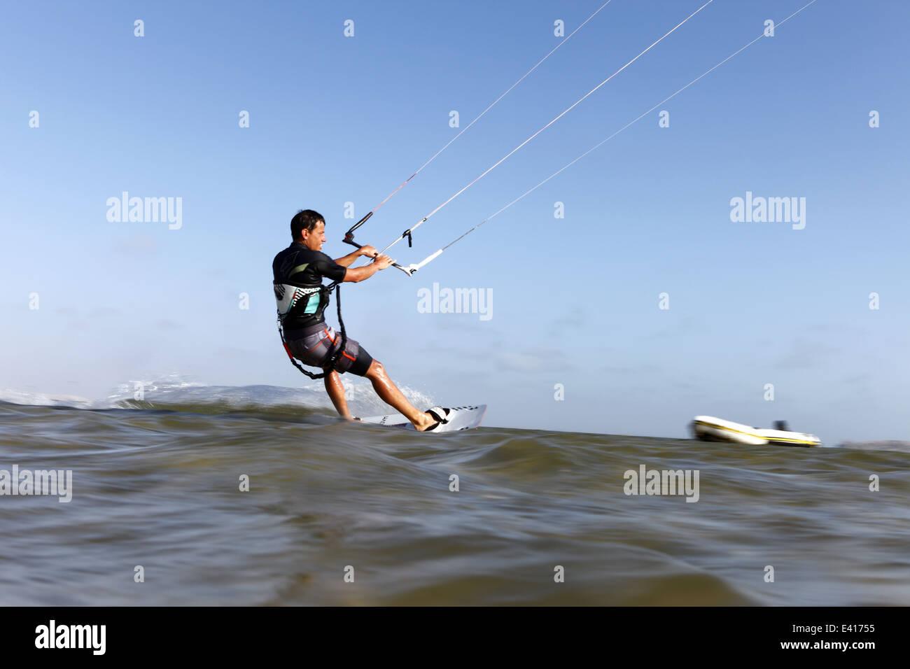 Man kitesurfing at speed on the horizon of the lagoon in Dakhla, Western Sahara, Morocco - Stock Image