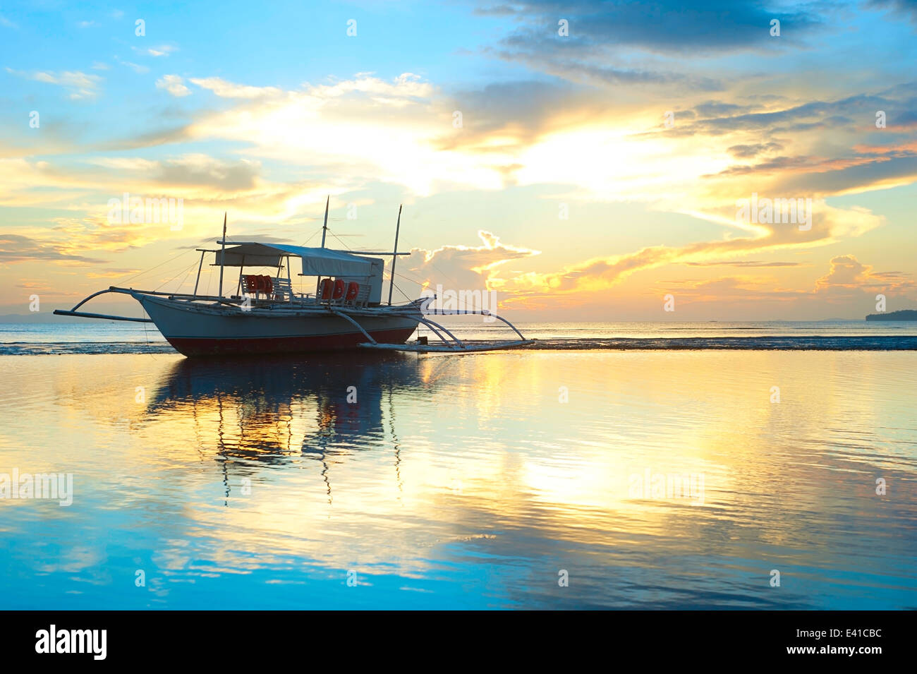 Tropical landscape with traditional Philippines boats at sunset - Stock Image