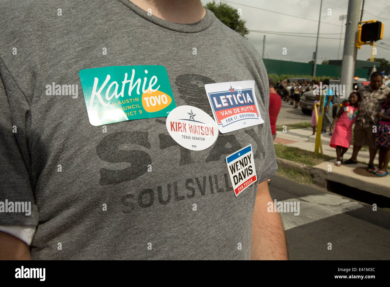 Male wears a t-shirt with stickers promoting several local and state-wide politicians and political candidates at - Stock Image