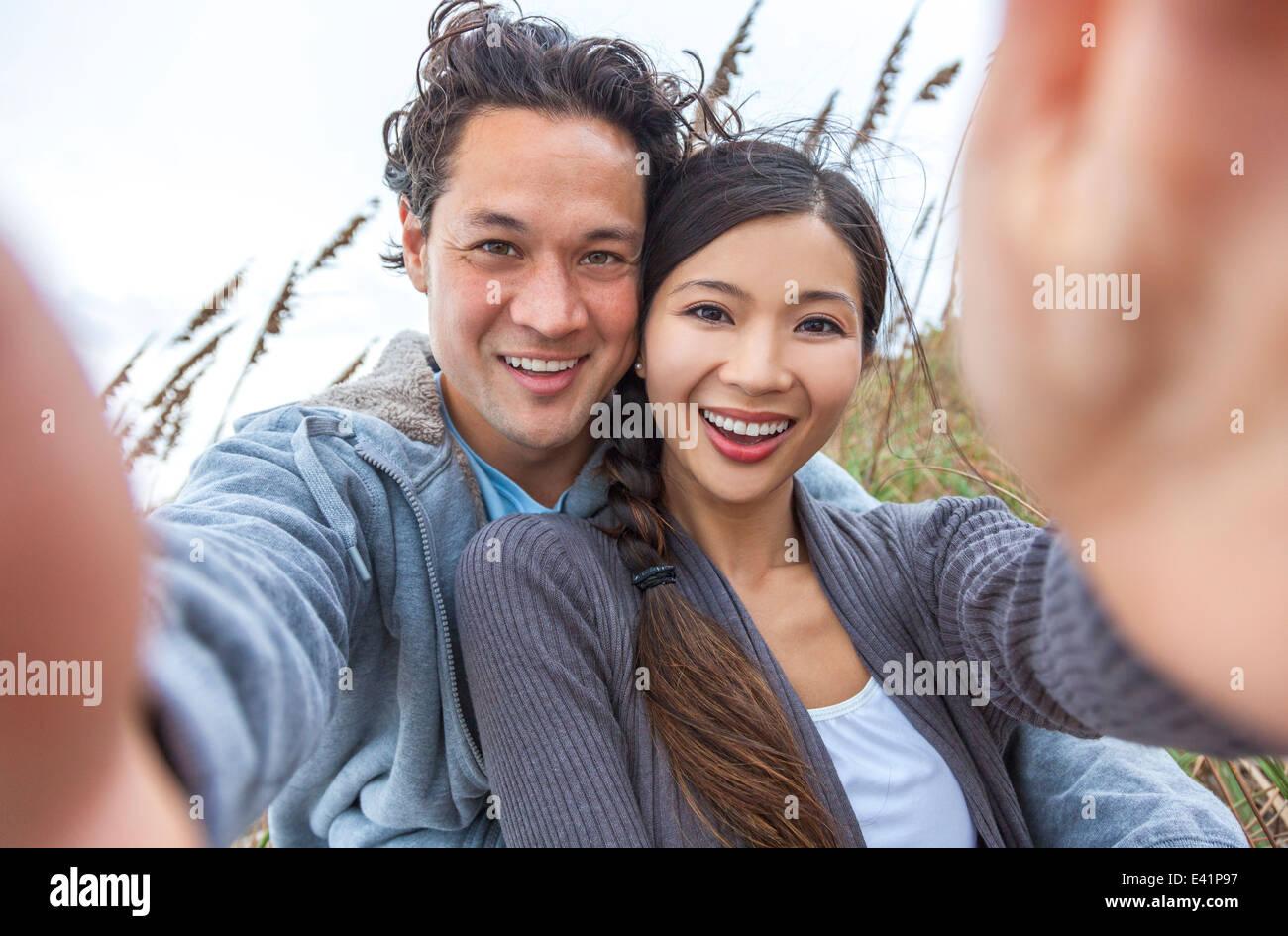 Man & woman Asian couple, boyfriend girlfriend in bikini, taking vacation selfie photograph at the beach - Stock Image