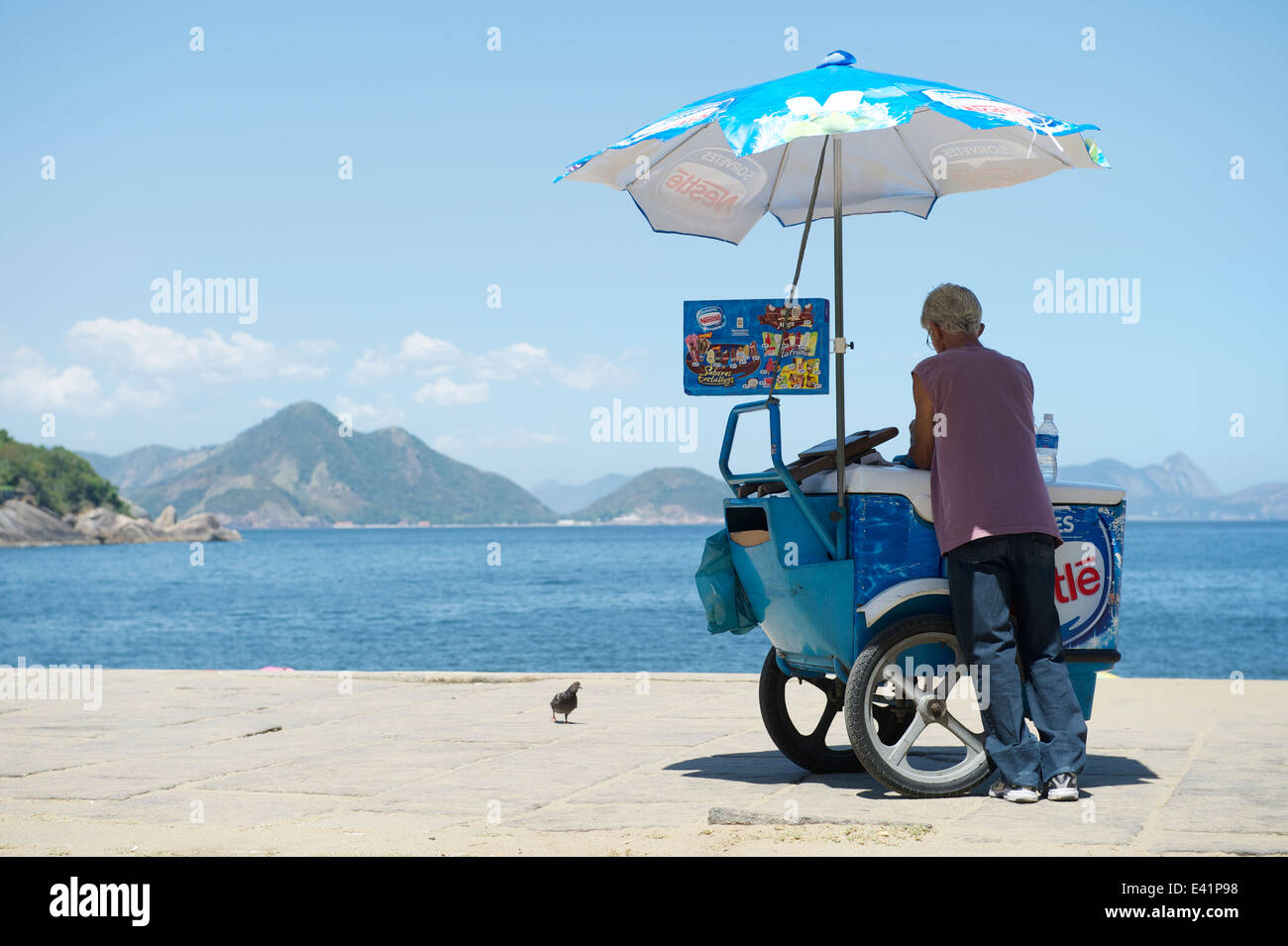RIO DE JANEIRO, BRAZIL - FEBRUARY 11, 2014: Brazilian beach vendor selling ice cream stands at the entrance to Red - Stock Image