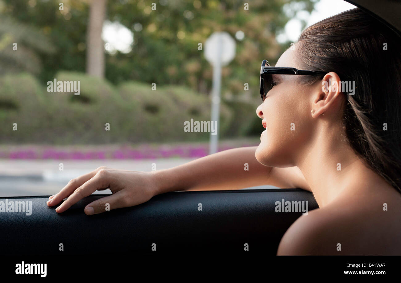 Close up of young woman looking out of taxi window - Stock Image