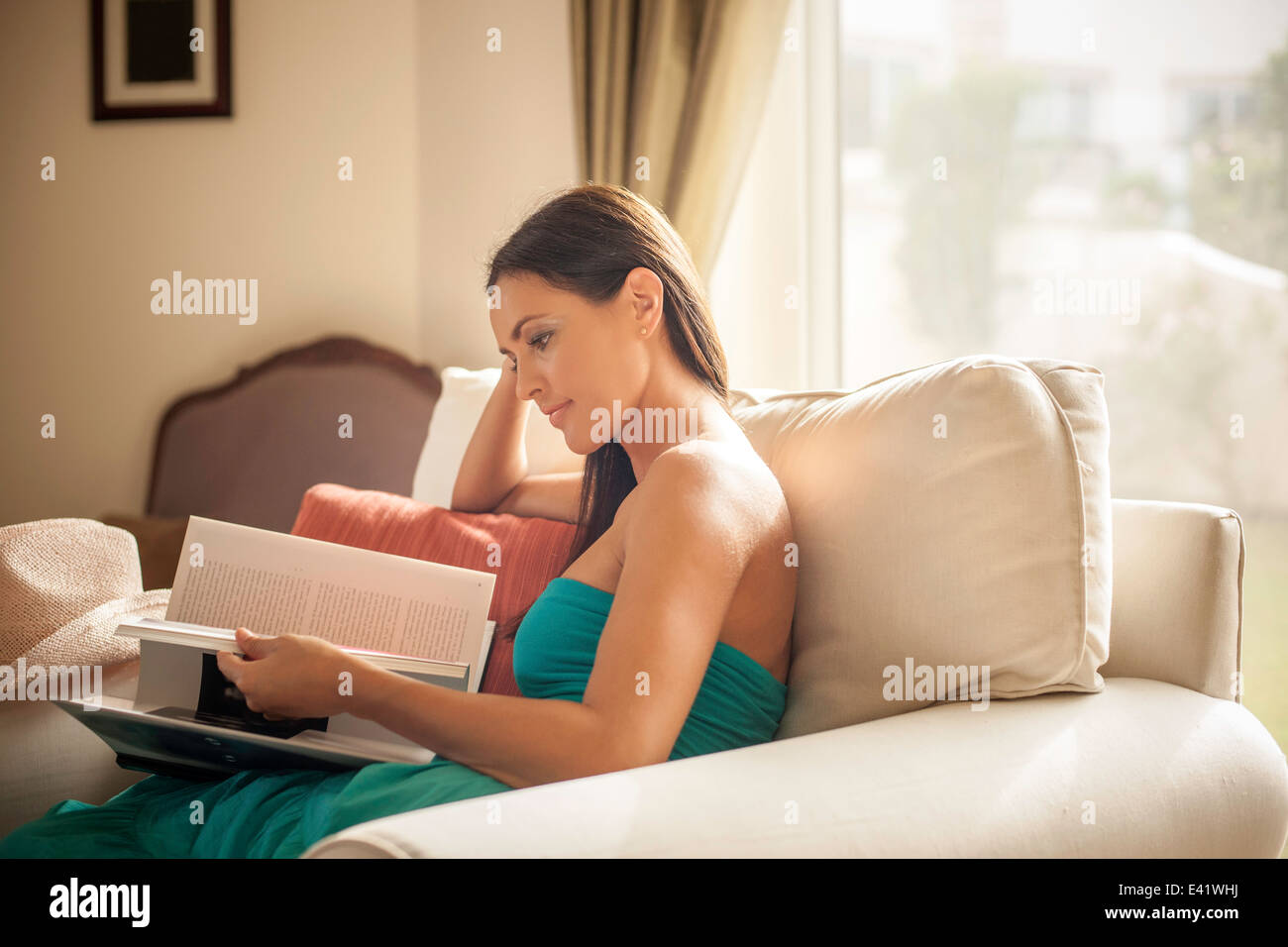 Young woman sitting in armchair reading book - Stock Image
