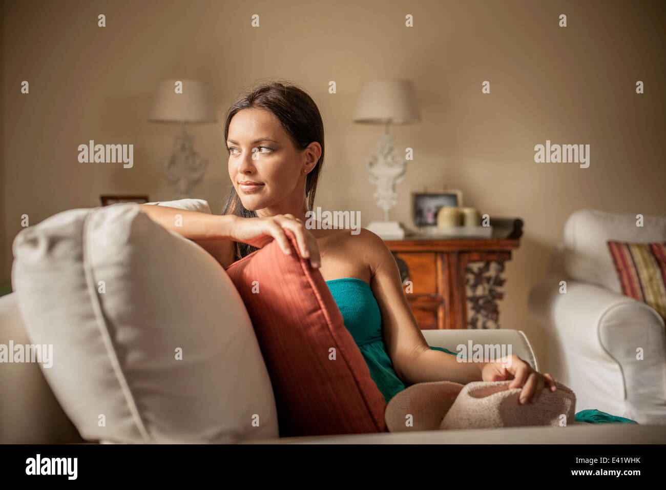 Young contemplative woman sitting in armchair - Stock Image