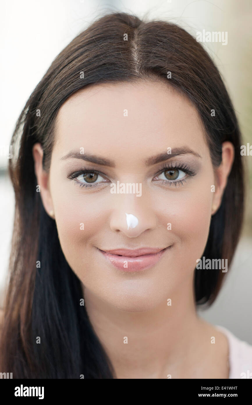Portrait of young woman with dab of cream on her nose - Stock Image
