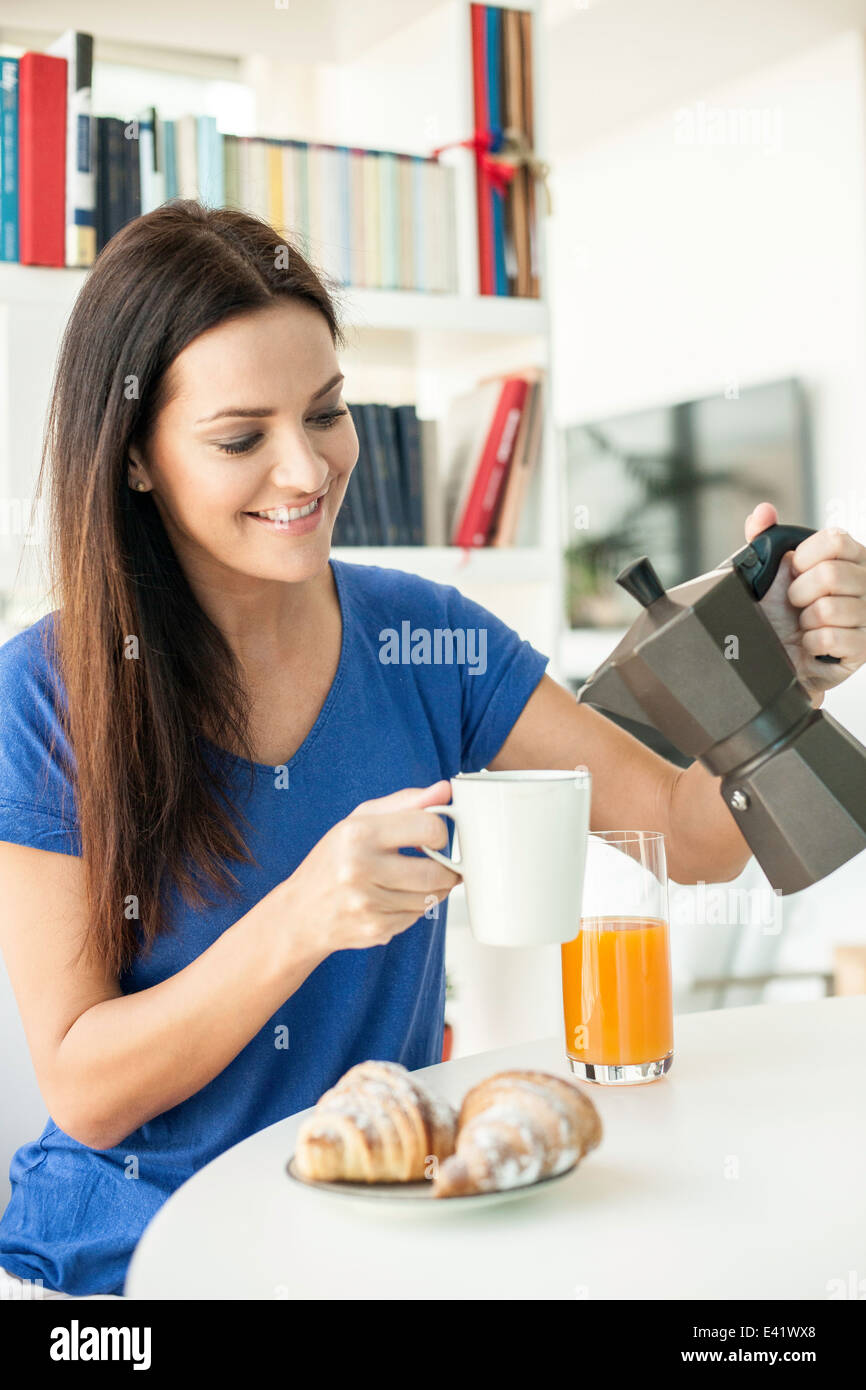 Young woman pouring coffee for breakfast - Stock Image